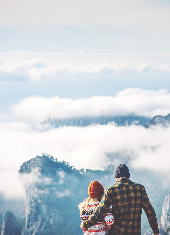 Couple lovers Man and Woman hugging enjoying mountains. And clouds landscape on background Love and Travel happy emotions Lifestyle concept. Young family royalty free stock photos