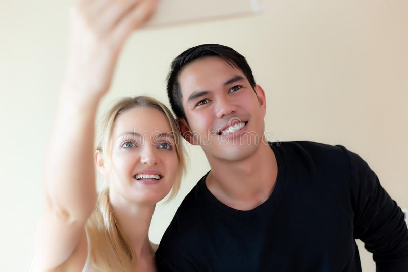 Couple or lovers selfie together by using smartphone for taking photo. Handsome young asian guy and beautiful young caucasian royalty free stock photo