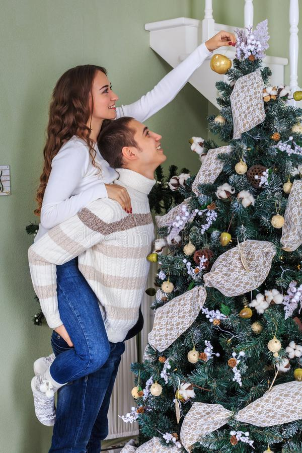 Couple of lovers trim a Christmas tree together on the eve of the Christmas holidays.  stock photo