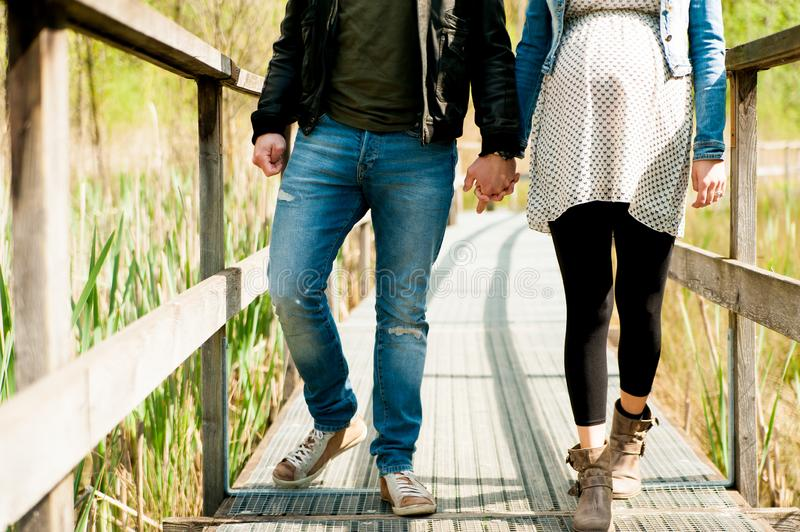 Young expecting couple, dressed in modern casual way, walking on wooden pier during sunny day in the woods, immersed in nature. Couple of lovers walking in royalty free stock photo