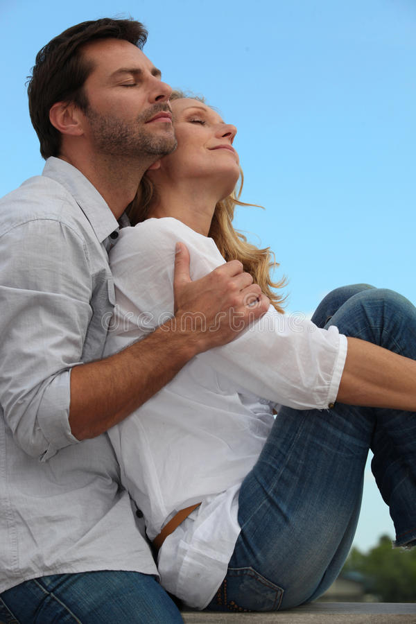 Couple in a loving embrace. Sitting in the sunshine stock photo