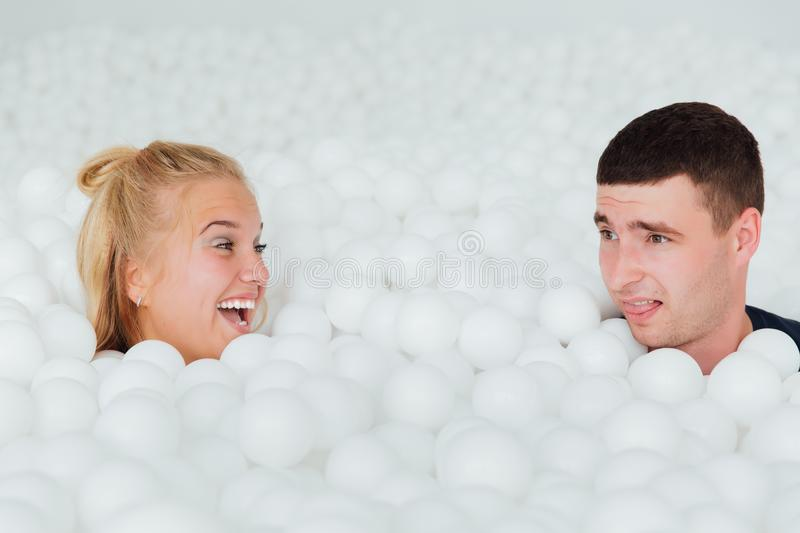 Couple of loving friends have fun surrounded by white plastic balls in a dry swimming pool. stock photo