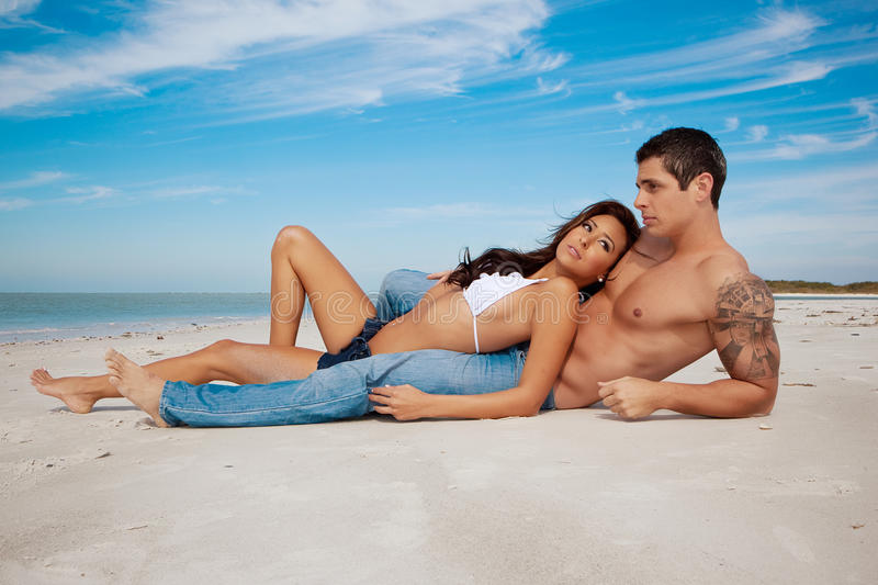 Couple lying on a beach stock images