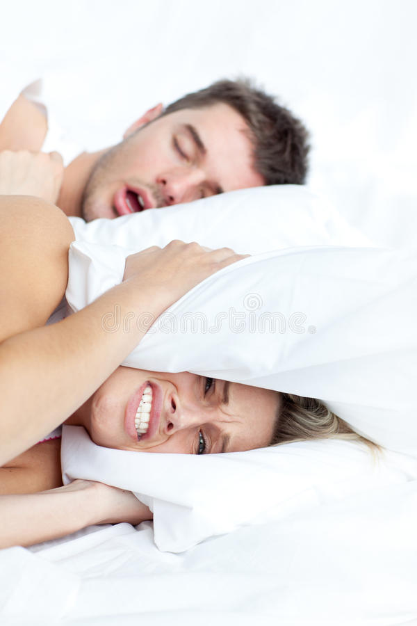 Couple lying on bed. Scenic in bedroom of loving young couple lying in bed and holding pillow on the ears because of snoring boyfriend