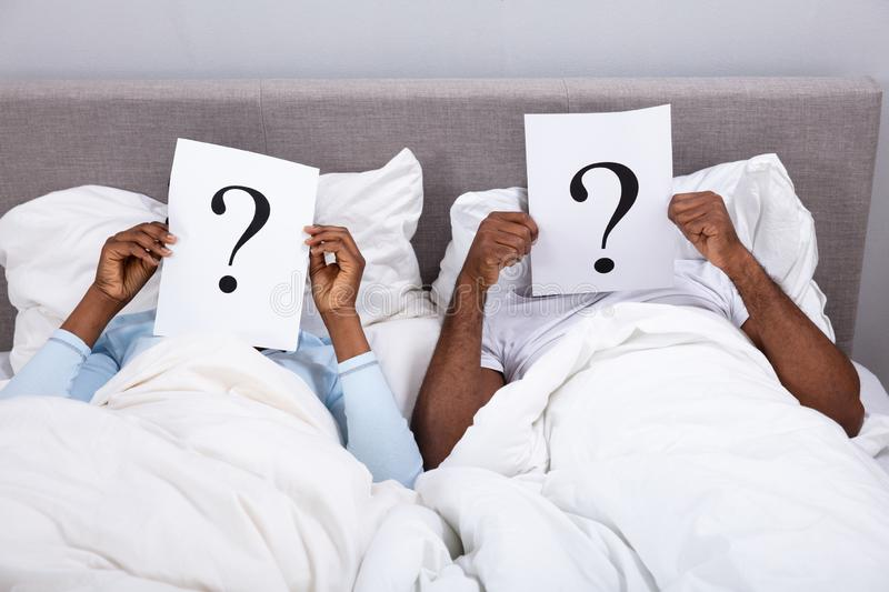 Couple Lying On Bed Holding Question Mark Sign stock photos