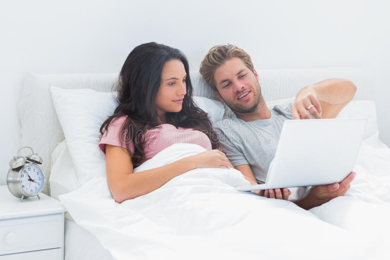 Download Couple Lying In Bed Looking At A Laptop Stock Photo - Image: 31801924