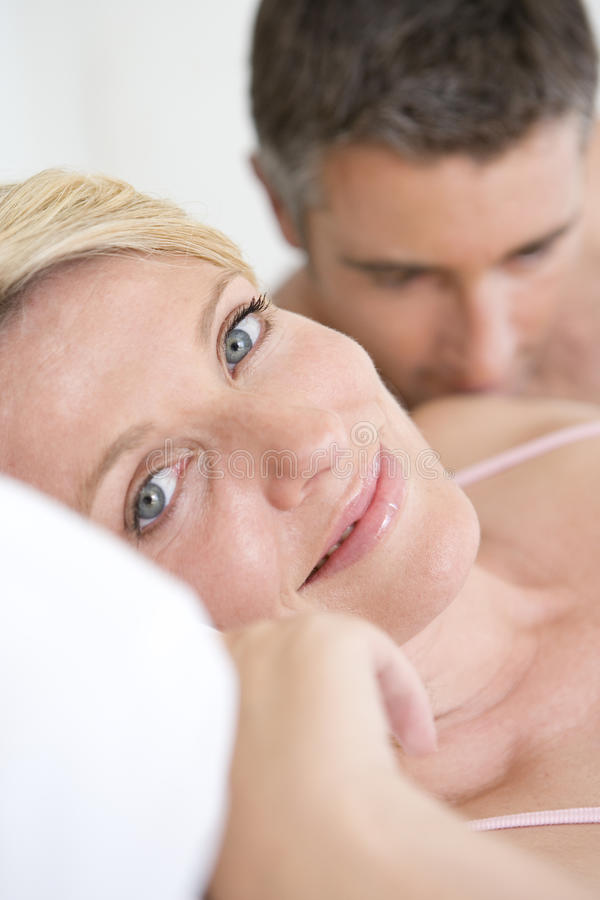 Couple lying in bed, portrait of woman smiling, close-up royalty free stock photo