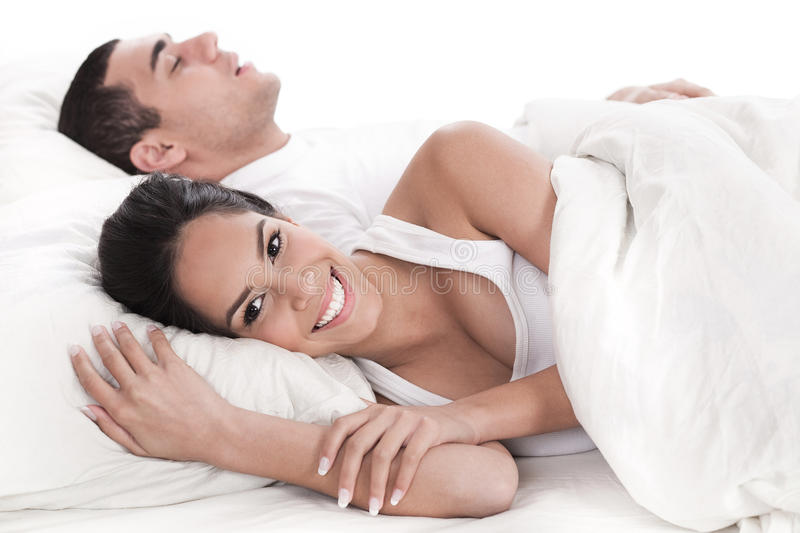 Couple lying in bed together, man sleeping. And woman smiling cover in white sheet stock photography