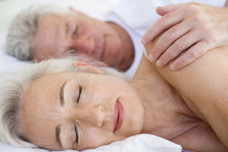 Couple Lying In Bed Together Sleeping Stock Photo