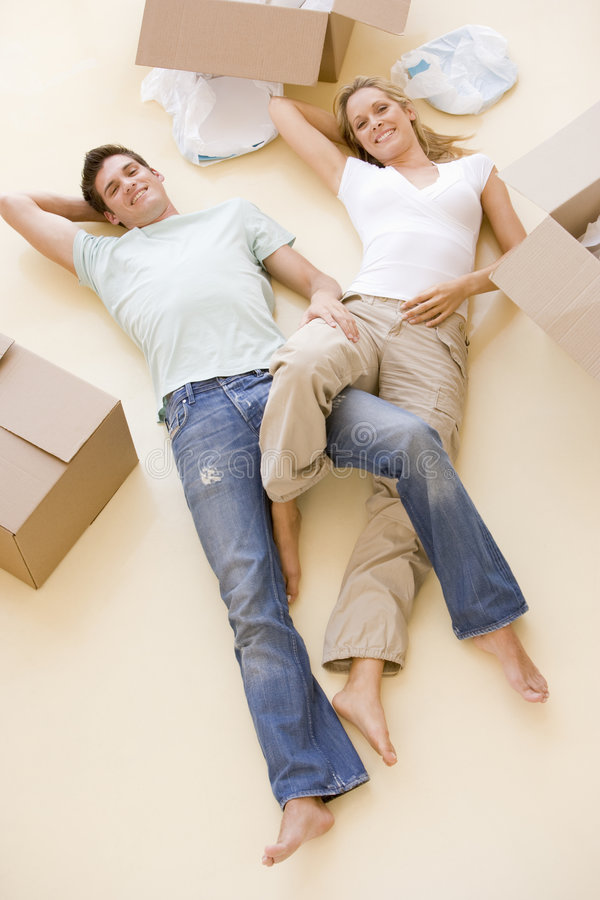 Couple lying on floor by open boxes in new home stock image