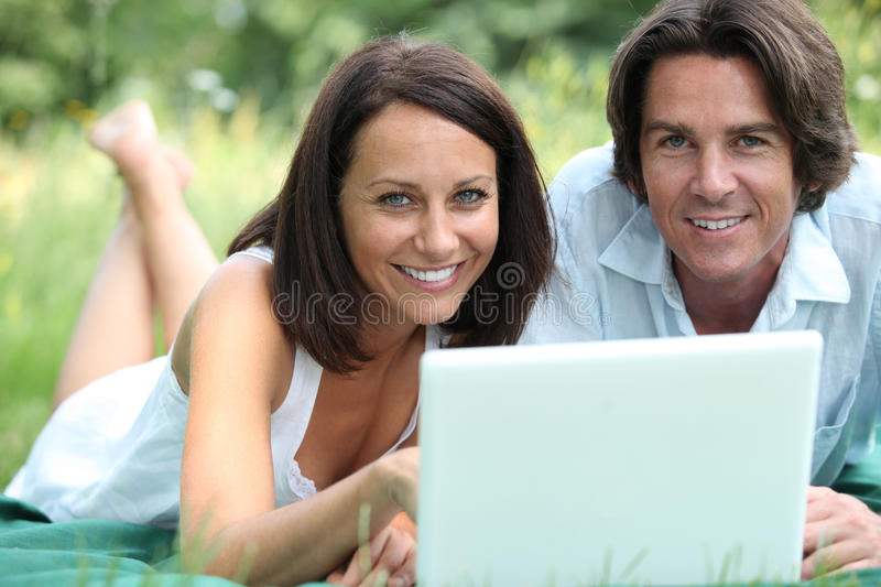 Couple with lying in the grass stock photo