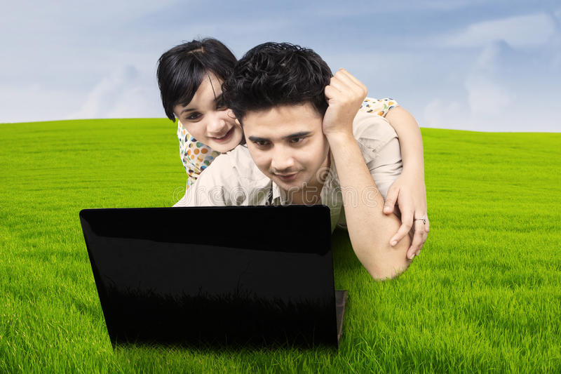 Couple Lying On Grass Looking At Laptop Stock Photo