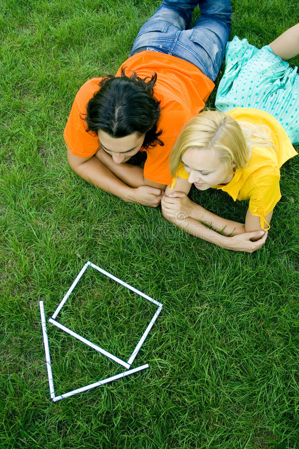 Download Couple Lying On Grass With Model House Stock Image - Image: 5939903