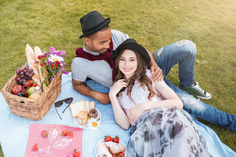 Couple lying and having picnic on lawn stock photos