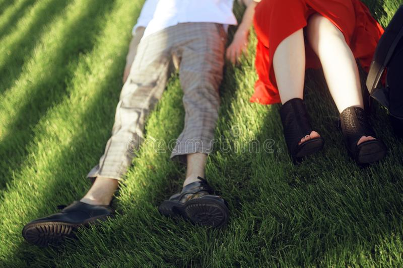 Couple lying and relaxing on the grass. Legs, top view. two pair of male and female legs in shoes lying on green grass. Very fashionable shoes. Photo for shoe stock photos