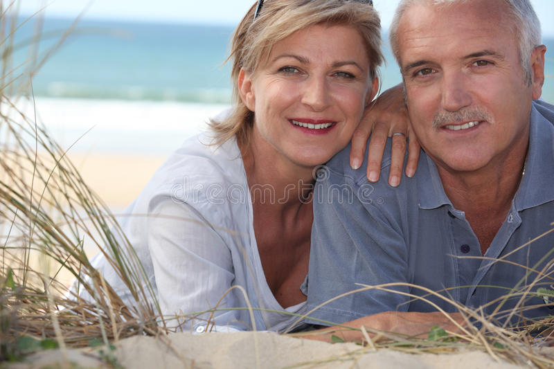 Couple lying in the sand dunes stock photography