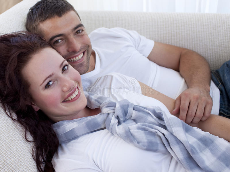 couple lying smiling sofa 免版税库存图片