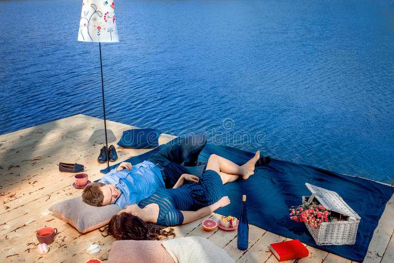 Couple lying on terrace near blue water. Couple lying on terrace near the water stock photo