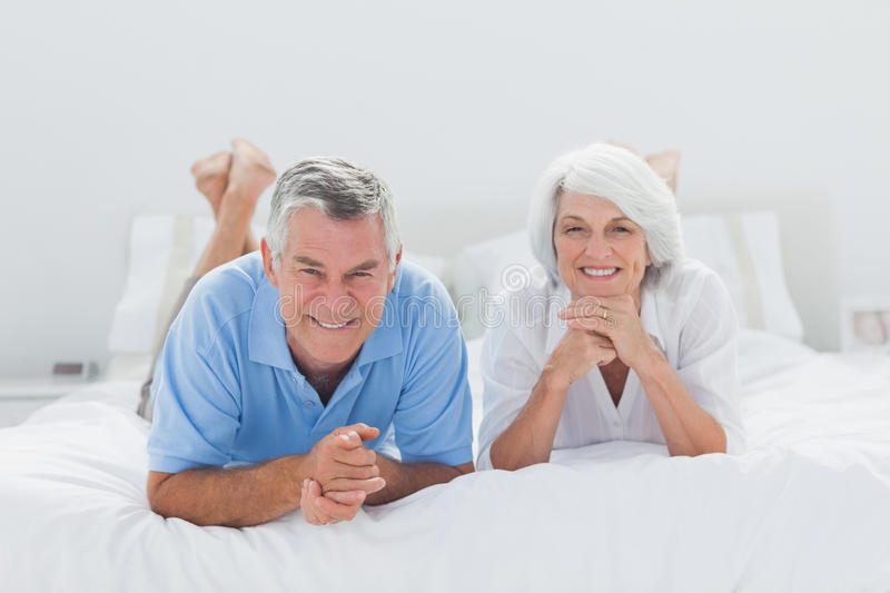 Couple lying together in bed stock photos