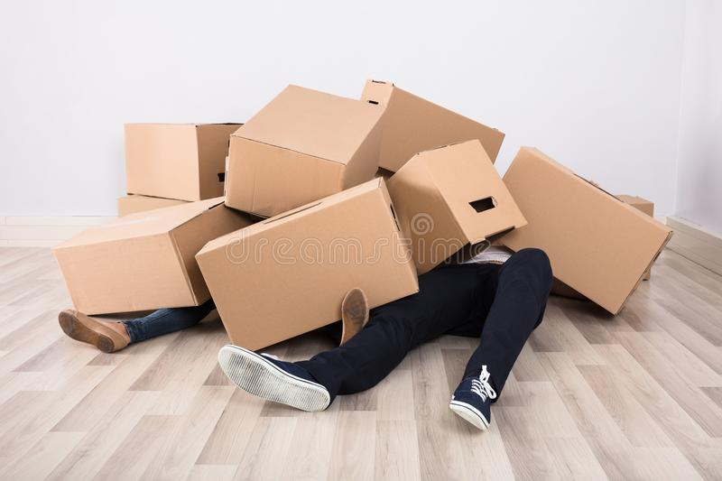 Couple Lying Under The Cardboard Boxes. Close-up Of Couple Lying Under The Heap Of Cardboard Boxes On Floor royalty free stock image