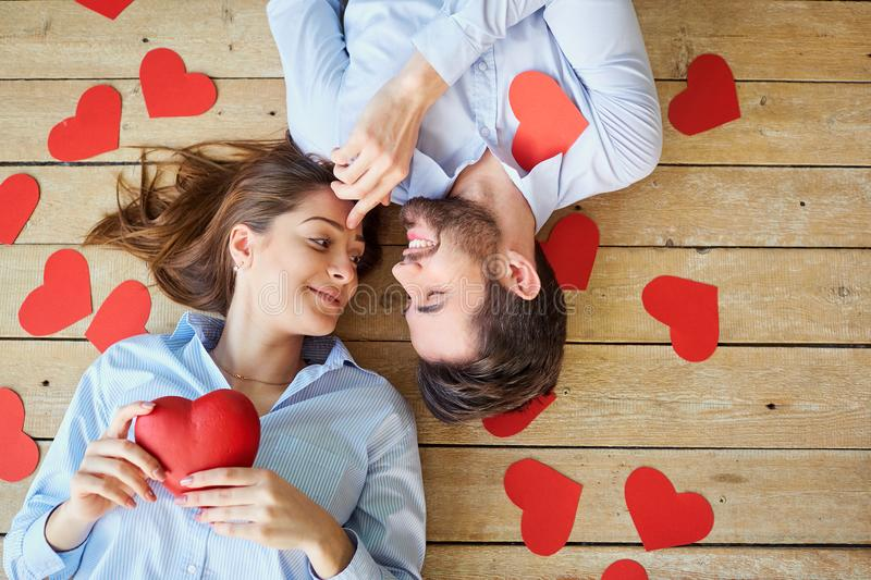 Couple lying on the wooden floor with hearts view from above. royalty free stock photography