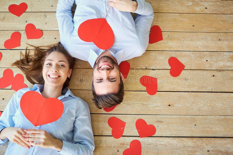 Couple lying on the wooden floor with hearts view from above. stock images