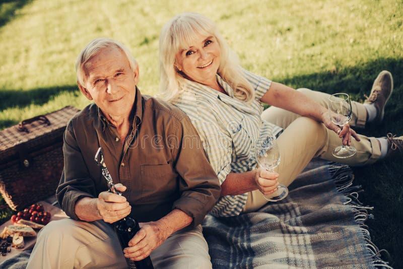 Couple mûr de sourire gai ayant le pique-nique dehors photo stock
