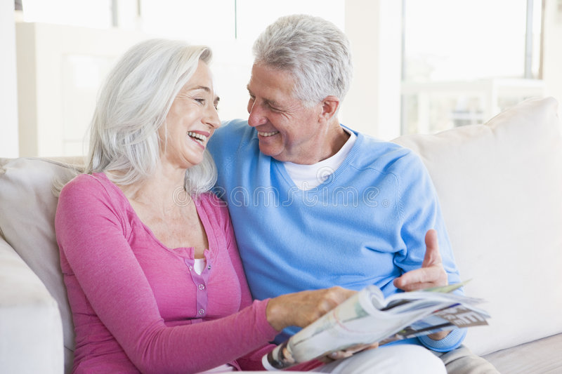 Couple With A Magazine Smiling Royalty Free Stock Images