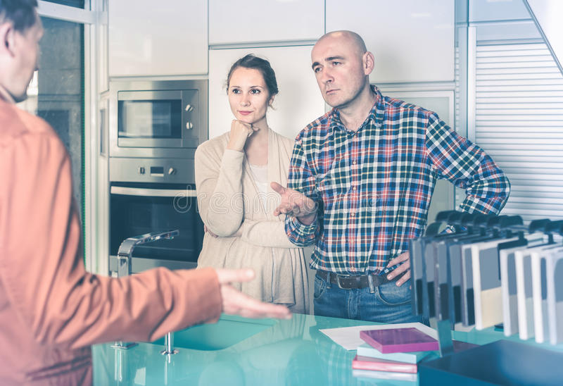 Couple makes claims at kitchen furniture workshop. Angry couple makes claims at kitchen furniture workshop stock photo