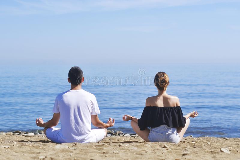 Couple makes meditation in lotus pose on sea / ocean beach, harmony and contemplation. Boy and girl practicing yoga at sea resort royalty free stock photo