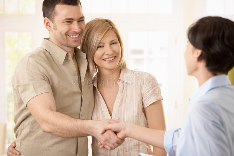 Couple making deal with agent stock photo