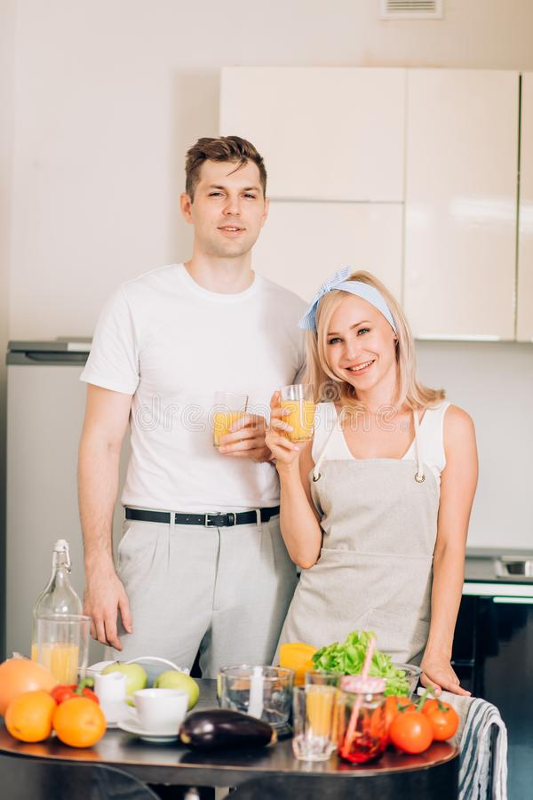 Couple making fresh organic juice in kitchen together royalty free stock images