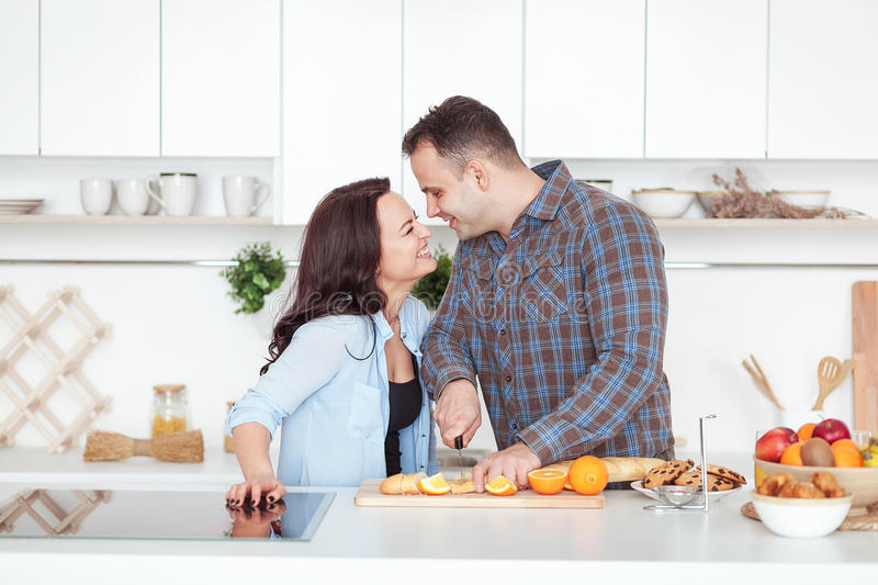 Couple making fresh organic juice in kitchen together. A young man slices a baguette. A woman standing near her royalty free stock photo