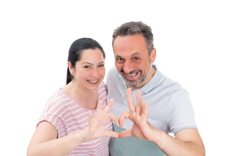 Couple making heart gesture with fingers. Cheerful men and women couple making heart gesture with fingers as love or romance concept isolated on white background stock image