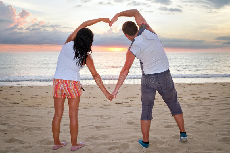 Download Couple Making Heart Shape With Arms At Sunset Stock Photo - Image: 27795388
