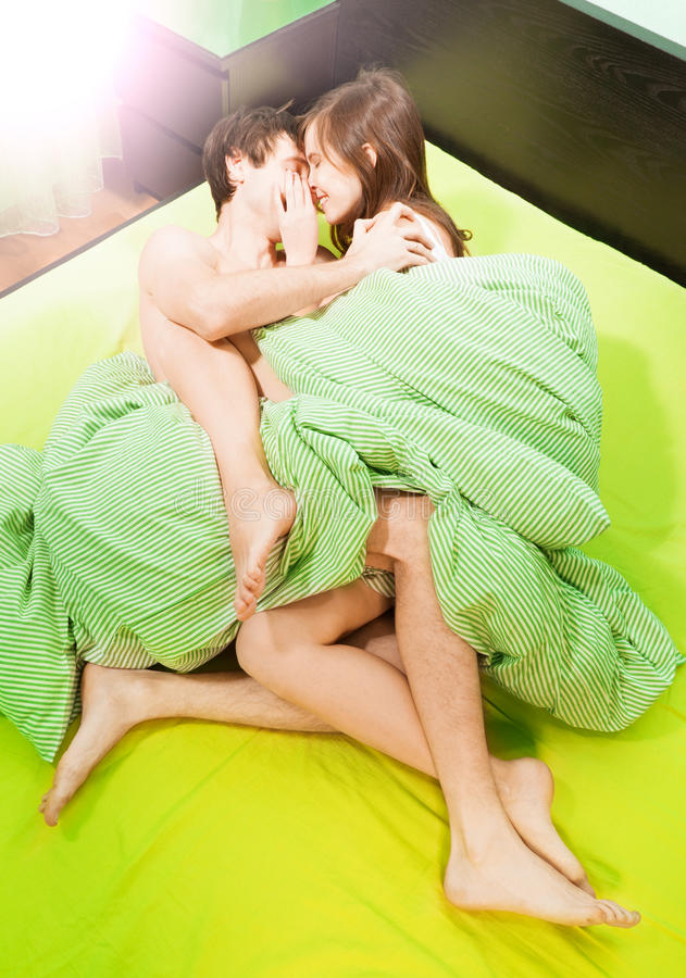 Couple making love in bed. Happy beautiful couple making love in bed royalty free stock photos
