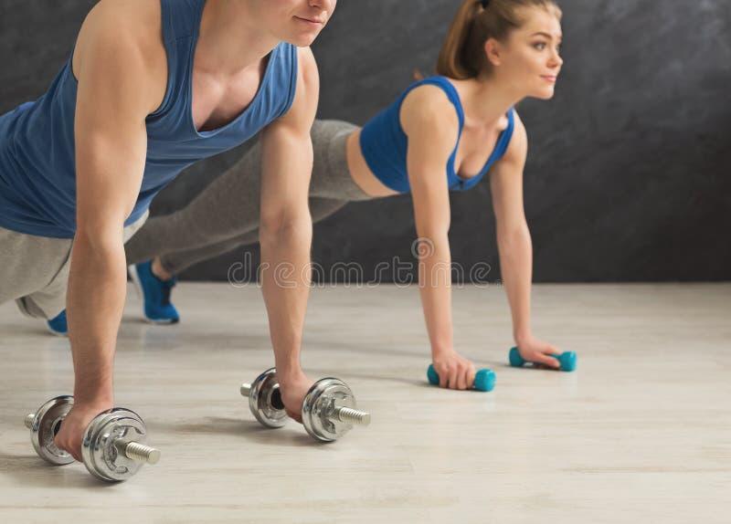 Couple making plank or push ups exercise indoors stock image