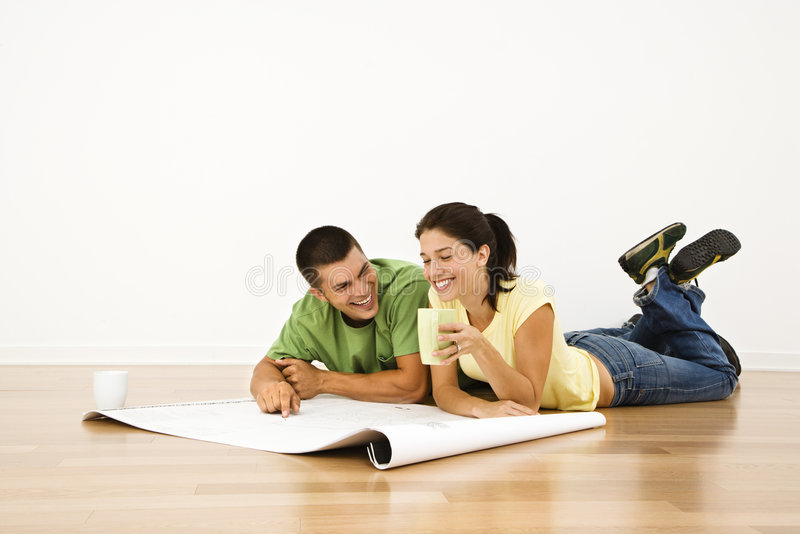 Couple making plans. Attractive young adult couple lying on home floor with coffee cups smiling and looking at blueprints stock photography