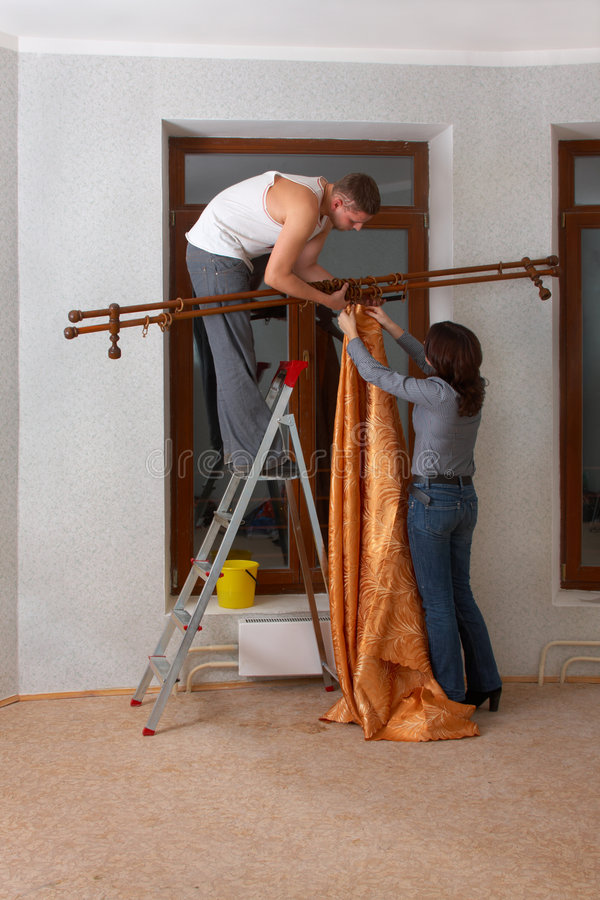 Couple is making repair. Hang up a cornice royalty free stock images