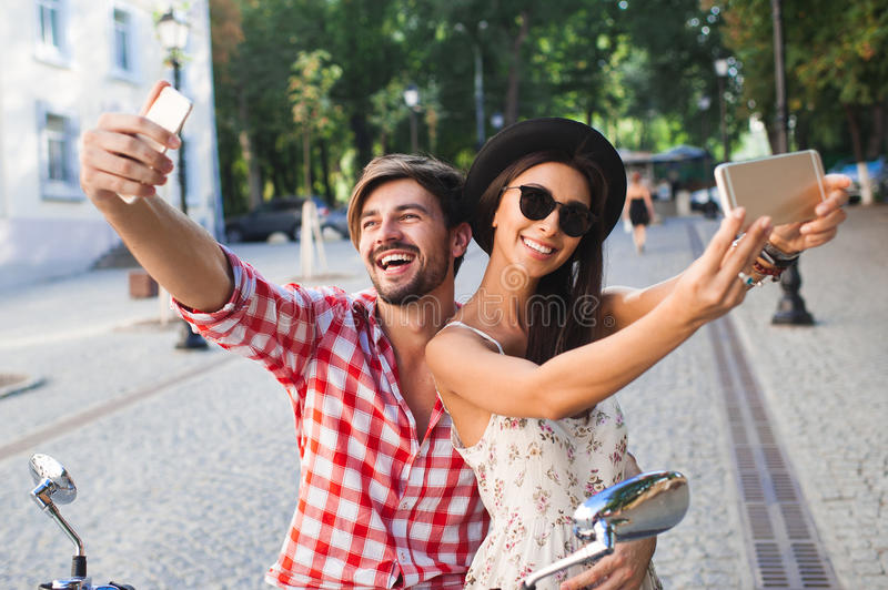 Couple making selfie photo. On a background of the city. Fashion young women and handsome men holding mobile phone and making self photos royalty free stock image