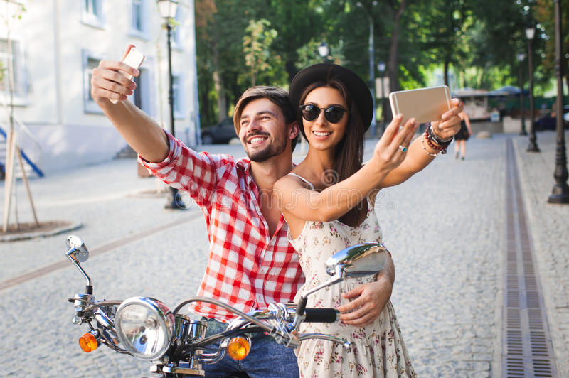 Couple making selfie photo. On a background of the city. Fashion young women and handsome men holding mobile phone and making self photos royalty free stock photography