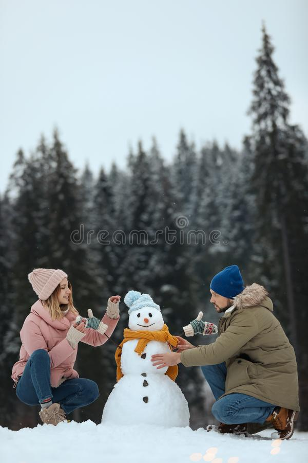 Couple making snowman near forest, space for text. Winter. Vacation royalty free stock photos