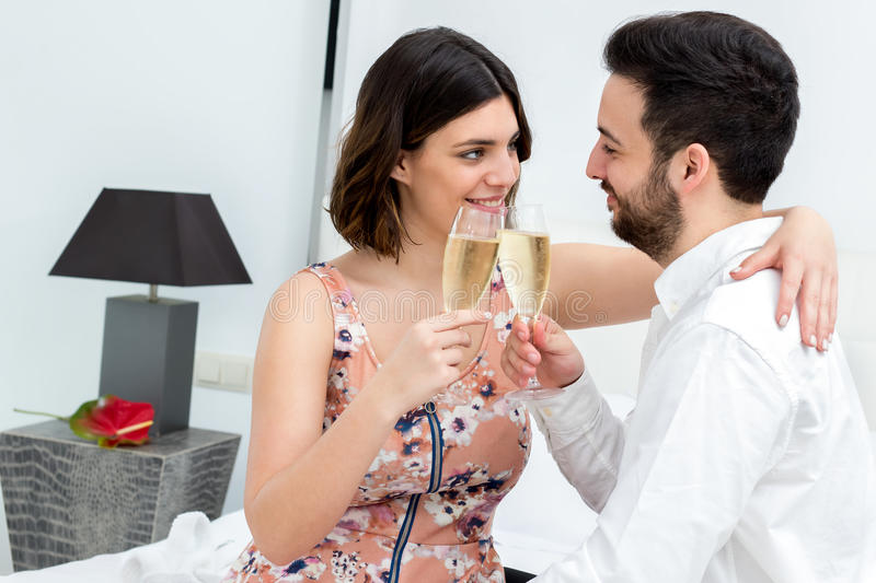 Couple making sparkling wine toast in hotel room. royalty free stock image