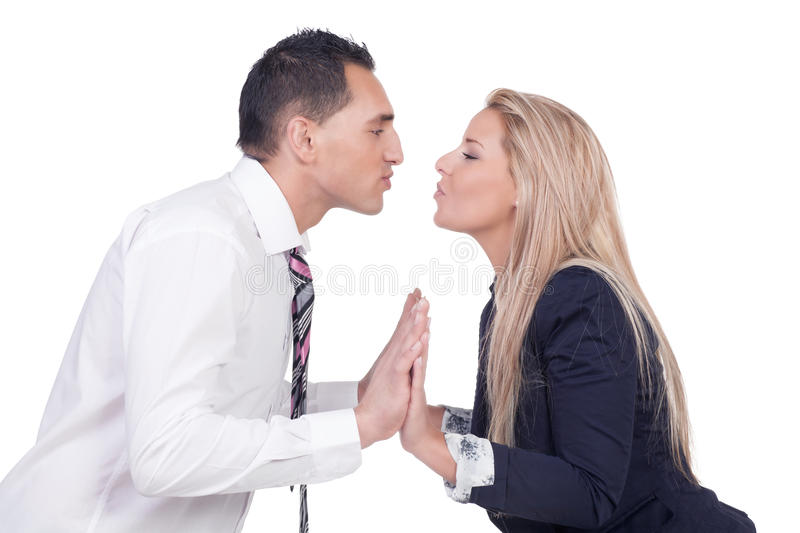 Couple making up and preparing to kiss. Young married couple making up after a disagreement and preparing to kiss leaning towards each other with their lips stock image