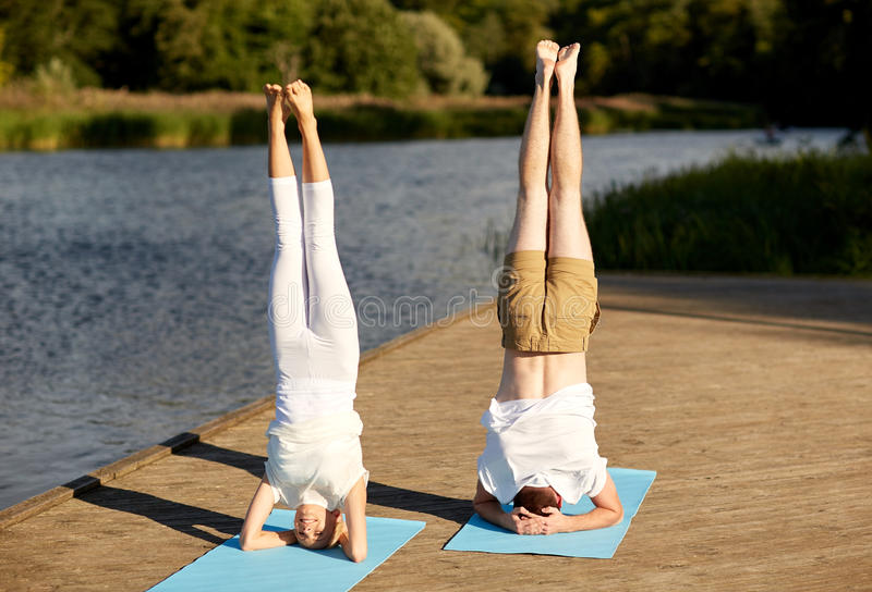 Couple making yoga headstand on mat outdoors. Fitness, sport, yoga, people and healthy lifestyle concept - couple making headstand pose on mat on river or lake stock images