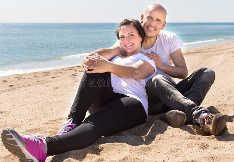 Couple of man and a middle-aged woman in white T-shirt sitting on the beach. Smiling couple of men and a middle-aged women in white T-shirt sitting on the beach stock photo