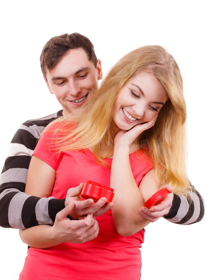 Couple. Man surprising cheerful woman with gift box. Couple and holiday concept. Handsome men surprising cheerful women with red heart shaped gift box isolated stock photo
