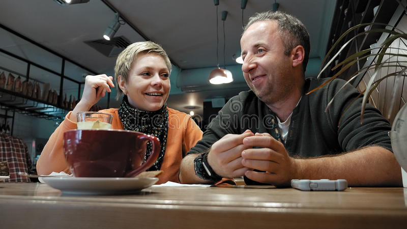Couple man and woman eats talks in cafe restaurant royalty free stock photography