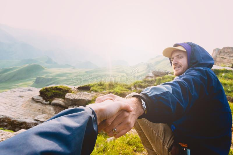 Couple Man and Woman holding hands follow enjoying caucasian mountains landscape on background Love and Travel emotions Lifestyle royalty free stock photography
