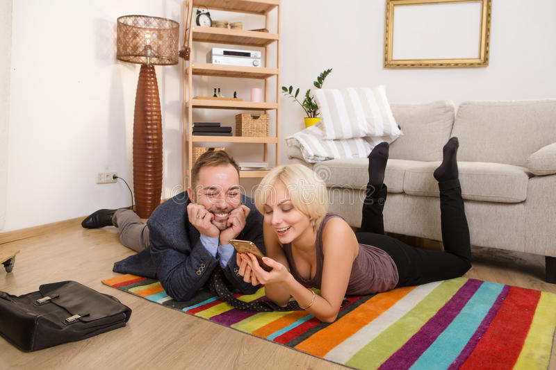 Couple man and woman lying on floor at home. Beautiful couple men and women lying on floor and smiling for camera. Man and women looking at smart or mobile phone royalty free stock photo
